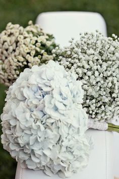 What if all the women in bridal party carried a simple bouquet of white flowers and each one was different. Then the bride's bouquet was made up of a combination of those flowers.