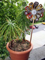 Turn a tin can lid, bottle tops and a chopstick into a cute garden flower with this #tutorial.