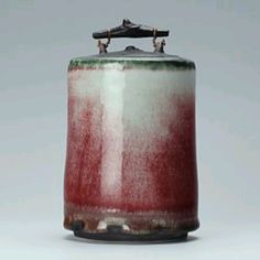 This is a thrown and turned lidded porcelain jar by Eddie Curtis which he has applied copper glaze then reduction fired.