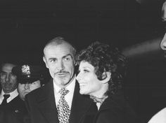 """March 11, 1976, the actress Audrey Hepburn (Signora Andrea Dotti) photographed with the actor Sean Connery during their arrival at the Radio City Music Hall in New York City, New York (USA), for a party following the premiere of their movie """"Robin and Marian"""". Audrey was wearing: Cape: Valentino (of black wool with a hood, of his couture collection for the Autumn/Winter 1970/71). Note: Audrey was wearing a ribbon of red satin on her neck by Valentino."""