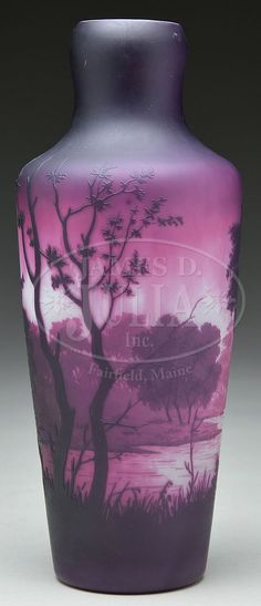 James D. Julia, Inc. -  D'Argental Cameo Vase. Unusual cameo vase is decorated in vibrant purple, rouge and pink on a white ground and shows a scene with large deciduous trees in the foreground and having a lakeshore in the background. The interior of the vase has a cased lining.