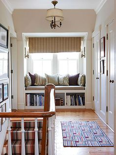 A cozy built-in window seat with shelving below tucked into the end of an upstairs hallway.