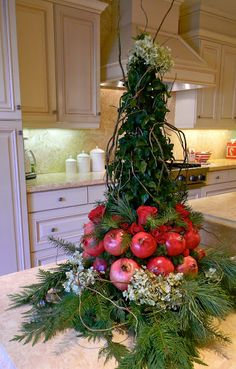 Monday, December 5, 2011  Holiday Home Tour - ivy topiary tree with pomegranates at the base, hydrangeas at the top of the tree and base with more evergreens. Red roses sit on top of the pomegranates. So pretty!.....
