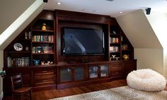 Problem solver (© Mosaic Group Architects and Remodelers) built in entertainment center in a bonus room under the eaves.