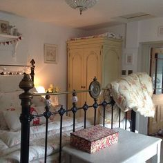 English country cottage bedroom with victorian bed and vintage eiderdown