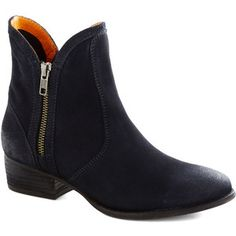 The Lucky Penny ankle boot by Seychelles features a statement side zipper, a low heel, and a dark navy blue suede upper