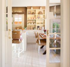 Entrada a cocina en tonos blancos a través de puerta corredera doble