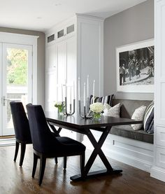 Transitional dining nook features a gray built in bench, flanked by floor to ceiling cabinets, facing a dark brown x based dining table lined with navy blue dining chairs.