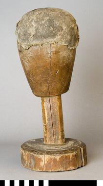"""""""Mösstock av furu. Skulpterat huvud med rakt fäste och rund sockel. Överdelen har lager på lager med klistrad linnelärft och paper."""" DigitaltMuseum - Mösstock"""