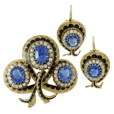 Victorian Enamel Sapphire Diamond Gold Jewelry Suite. This magnificent Victorian jewelry suite consists of a pendant-brooch and a pair of earrings featuring an intricate filigree design hand-crafted in 18k yellow gold and contrasted with black enamel. This suite is beautifully prong-set with natural unheated faceted blue oval sapphires - an estimated 19 carats in the brooch and 5 carats in the earrings and accented with sparkling mine-cut diamonds - an estimated 4 carats in the brooch and 2…