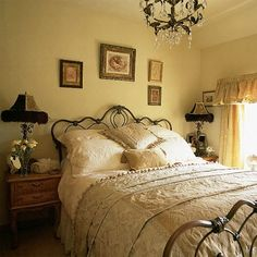 The combination of mellow yellow walls and curtains is calming and the pretty iron bed from Housing Units with delicate Marks & Spencer bedding adds a romantic touch to this bedroom. Twin feather-trimmed lamps, a crystal chandelier and old framed pictures continue the vintage theme. Designer: Housing Units