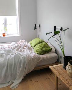 Kombiner strandbeige sengesett med mosegrønne puter.