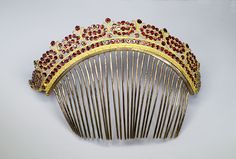 Gorgeous comb with a crown shaped heading, decorated with numerous ruby gemstones mounted on gilt silver.  French Empire.