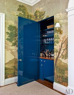 A bar hides within a dining room wall; the sconce is from Circa Lighting.