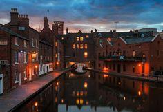 A canal runs through old, industrial buildings in Birmingham, England.