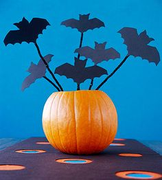 Winged Invasion:   You'll fly through putting this bat centerpiece together. Cut out the bats. Cut black chenille stems to different lengths so the bats will be at different heights. Tape one stem to the back of each bat. Place a piece of dry florist's foam inside a hollowed out pumpkin, and stick the stems into the foam; arrange so bats appear to fly out of the pumpkin.