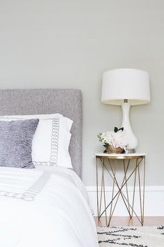 Simple and cozy, this bedroom features a round marble and brass bedside table wi. Simple and cozy, this bedroom features a round marble and brass bedside table with a milk glass gourd lamp beside a gray headboard. Bedside Table Inspiration, Bedroom Inspiration, Bedside Table Decor, Cool Bedside Tables, Grey Headboard, Headboard Lamp, Side Tables Bedroom, Home Decor Bedroom, Bedrooms