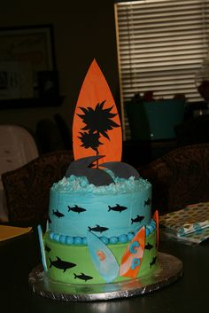 Shark and surfboard cake. Sharks are made using the sugar sheets from Wilton and cricut. Like the design and use of black with color.