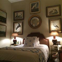 Guest bedroom with art arrangement over dark upholstered headboard