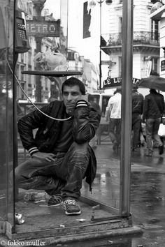 Man with an annoyed facial expression kneeling down listening to some one speak in a phone booth. The street is very dirty. B.