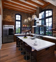 exposed brick, wood floors, exposed slanted beams, huge windows, open shelving, professional gourmet stove, huge island with bar stools... i am smitten.