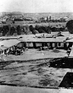 """(1857)* - View of Abel Stearns adobe known as """"El Palacio"""", located on the southeast corner of Main and Arcadia streets. Stearns purchased the land from Francisco O'Campo and built his adobe. He gradually expanded the adobe from 1835-1838, and the home eventually became U-shaped with a wide-open cobblestone court, and contained a grand ballroom at least 100 feet long. At the time, it was the largest and most magnificent house in the pueblo, which the natives gave the name of """"El Palacio de…"""