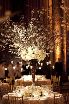 majestic! Wedding centrepiece - tall narrow vase with twigs, flower cluster and delicate blossom style flowers.