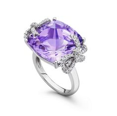 Purple amethyst center stone set within 18ct white gold and decorated with elegant diamond ribbons.