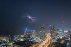 Dramatic: Tom captured this bolt of lightning above the Toronto skyline in his series of photographs called Rooftopping