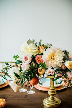 Designed by Juli Vaughn, this decadent Flemish-style floral arrangement featured dinner-plate dahlias, garden roses, dusty miller foliage, and fresh pomegranates. | Photo by Betsi Ewing