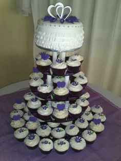 White and purple wedding cake covered in buttercream icing and white fondant with purple flowers en silver hearts.