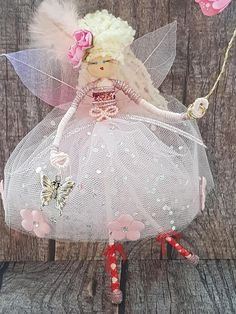 Say Hello to beautiful Miss Nixie, she has a pretty pink dress, little pink ballet shoes with red ribbons, a feather and roses in her hair and she is carrying her little pet butterfly! She stands approximately 8 tall, and can be hung in a little girls bedroom or as a decoration in any
