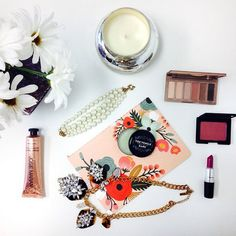 how to style instagram photos like a blogger: the flatlay, shoot from an birds-eye view - floral illustrated rifle paper co. notebook shot with flowers, a silver candle + jeweled statement necklace and makeup