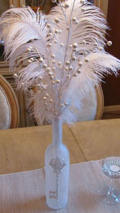 Simple but elegant for Christmas; wine bottle with glitter, beads, feathers, and key ornament' i would like to make this for my bedroom with peacock feather as well. Wine Bottle Centerpieces, Wedding Centerpieces, Wedding Decorations, Diy Masquerade Decorations, Feather Decorations, Masquerade Centerpieces, Wedding Ideas, Trendy Wedding, Wedding Table
