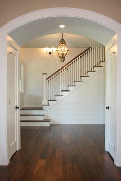 Great entry...love the white walls & trim paired with the dark wood and arched ceiling.