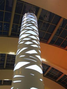The Strand Tower is an illuminated pillar formed by a metal shroud with a custom perforated pattern, borrowed from Arktura's Strand furniture collection. Columns Decor, Interior Columns, Mall Design, Retail Design, Luxury Interior, Modern Interior Design, Column Lights, Column Wrap, Pillar Design