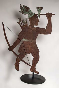"""Silhouette Indian weathervane with cut out eyes. Made of metal and copper. Constructed of multiple pieces of iron riveted together with sheep copper used for the hatchet, belt, arrows and feathers. Weathered and oxidized showing the natural pitting and verdigris surfaces.  New England, c.1900.   35"""" H, 11 3/4""""diameter base."""