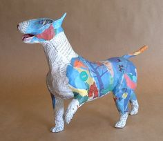 """This free standing bull terrier is made of paper and wire. No paint is used. Magazine paper is used for its durability and to ""paint"" this lively and whimsical dog sculpture."""
