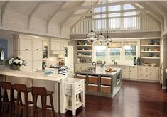Kitchen all in white with loft ceilings, bar seating, and industrial accents