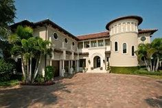 A Mediterranean style home. A stucco facade with cast stone accents and a unique column/banding at the roof. Mediterranean Style Homes, Cast Stone, Historic Homes, Art Deco Fashion, Home Buying, It Cast, Mansions, House Styles, Design