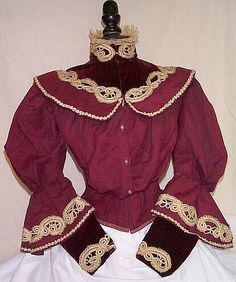 """C.1896-1897. made of wool with the softest silk velvet trim you have ever felt. Soustache braid adds a bold contrast to the bodice. This bodice would have been worn during the winter time and is lined in striped cotton ticking. It's fully boned with 7 bones and has a waistband inside. The bottom of each sleeve puff have a sweeping pagoda sleeve style skirt in which the velvet """"undersleeve"""" comes out of. The high standing velvet collar also has a lace trim around the top to flatter the throat"""