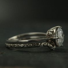 This is one of my favorites! I just love the North/South/East/West orientation of the delicate prongs and the vine detail along the side of the setting. Hand made from a precast solid Sterling Silver setting, your ring will be custom sized and set with an 8mm Cubic Zirconia, White Topaz, or Forever Brilliant Moissanite. It is paired with our Rococo band that is custom curved to fit up against the engagement setting. The band measures 2mm wide by 1.3mm thick and is hand made fro...