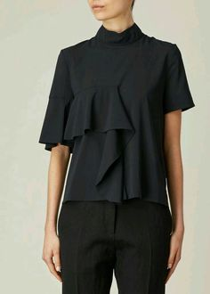 Short-sleeved mock neck ruffle front top in black stretch silk georgette. Draped ruffle embellishment at front. Hidden zip closure at back of neck. Fashion Details, Fashion Tips, Fashion Design, Mode Top, Black Ruffle, Blouse Designs, Shirt Blouses, Blouses For Women, Style Me