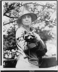 """Grace Coolidge: the First Lady kept a raccoon named Rebecca in the White House. """"Mrs. Calvin Coolidge, half-length portrait, standing, facing front, holding her pet raccoon."""" Taken between 1921 and 1923. Library of Congress, National Photo Company Collection."""