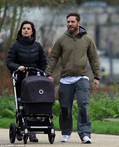 Happy parents: Actor Tom Hardy, 38, was spotted enjoying daddy duties as he took a walk with wife Charlotte Riley, 33, and their newborn baby on Sunday