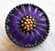 This is for one 18mm Czech glass sunflower button. It purple. amethyst, tanzanite glass with gold accents. It is a decorative floral shank button. It would make a great button for a wrap bracelet or a
