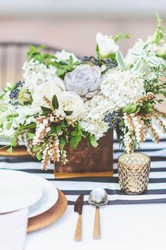 This reception-table arrangement features tons of textural elements, like peegee hydrangeas, pieris japonica, and privet berries, in a square wood vessel | Brides.com