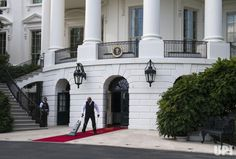 An usher vacuums the red carpet prior to the arrival of South Korean President Moon Jae-in and his wife Kim Jung-sook at the White House in…