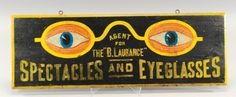 """""""SPECTACLES & EYEGLASSES"""" SIGN  c. 1870, fabulous wood sign, painted eyeglasses with peering eyes, black background brings out the vibrant colors, trimmed in yellow frame, double sided sign. 35"""" l."""