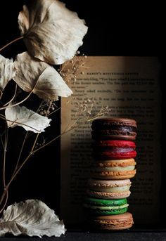 Macarons shot in a dark and moody setting with a play of lines, rustic dried flowers and a book adding to the mood, and a stunning curve created with light and shadow through the stack of macarons. Rustic Food Photography, Cake Photography, Food Photography Styling, Food Styling, Healthy Food To Lose Weight, Tuna Recipes, French Food, Creative Food, Food Art
